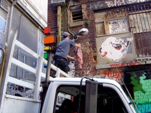 Snyder pasting up in Hosier Lane.
