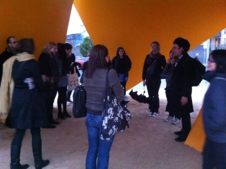 A sculpture tour takes shelter under Vault during a sudden shower.